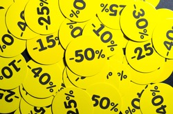 Yellow round stickers with discounts of 10 to 50 percent. Sell-out. Discounts on a black background. Black Friday. Price fall. Posters. Macro discounts