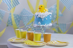 Yellow rubber duck themed birthday cake. Party background.
