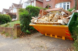 Yellow rubbish skip on driveway. Selective focus on full skip with space to add text in front of bin, footpath & blurry background of green bush fence, houses, brick wall. Renovate, moving concept.