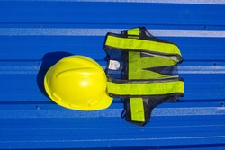 Yellow safety helmet  and safety reflective vest  on blue background., metal sheet background