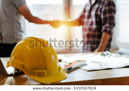 yellow safety helmet on workplace desk with construction worker team hands shaking greeting start up plan new project contract in office center at construction site, partnership and contractor concept stock photo