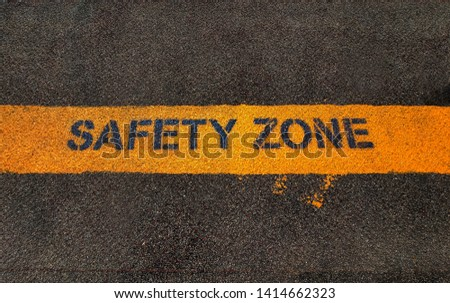 Yellow safety zone text on dark grunge asphalt tarmac surface created using spray painting color. Sign for passenger  on road to aware for traffic and vehicles movement.