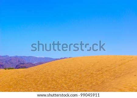 Yellow sand dune Landscape with  lilac mountains at the horizon under blue sky