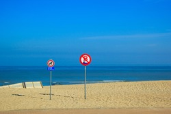 Yellow sand on the beach and blue sea. Sunny day, blue sky. Sign with the image of a dog.