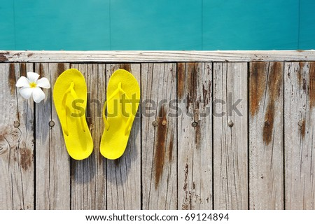 Yellow sandals by a swimming pool - stock photo