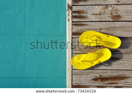 Yellow sandals by a swimming pool