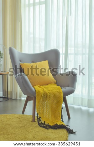 Yellow scarf and yellow pillow setting on gray color easy armchair in living room
