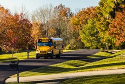Yellow school bus driving along a suburban street in the fall; trees and the sky in the background; Missouri, Midwest