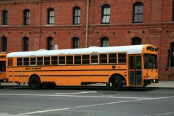 Yellow school bus in front of a red brick wall on a street in San Francisco .