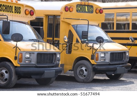 Yellow school buses parked in lot. - stock photo
