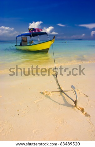 Yellow Scuba diving  boat anchored up on tropical beach