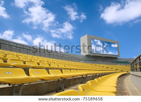 yellow seats and electronic billboard display at stadium