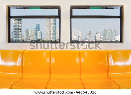Yellow seats in electric train with view from the windows