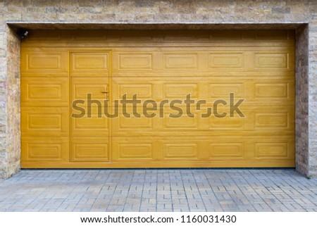 Yellow sectional garage door. Horizontally framed shot. #1160031430