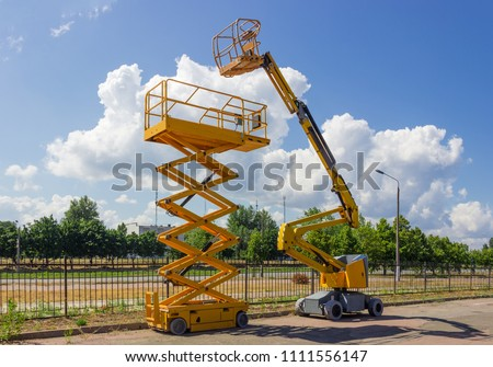 Yellow self propelled articulated boom lift and scissor lift on background of street with trees and sky