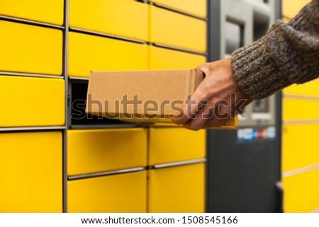 Yellow self-service post terminal machine. Man recieve a parcel