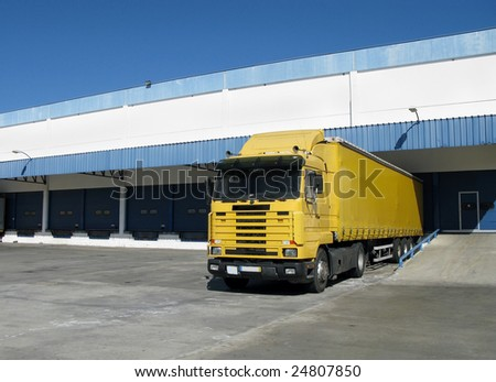 Yellow semi truck sitting at a loading dock