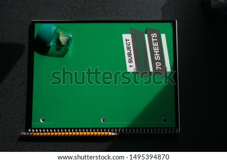 Yellow sharpened pencil in spiral of green wire-bound one subject notebook and green pencil sharpener in moody light with shadows on charcoal background #1495394870