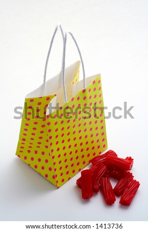 Yellow shopping bag and pieces of red licorices on white background