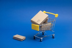 Yellow shopping cart or trolley and small , Product box, Package box , Isolated on blue background .Shopping symbols in shopping malls and general business concept.