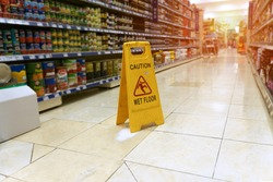 Yellow sign - caution. Wet floor is in the supermarket against the background of blurry products standing on the shelves