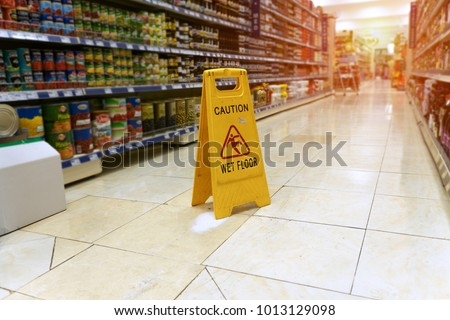 Yellow sign - caution. Wet floor is in the supermarket against the background of blurry products standing on the shelves Stock photo ©