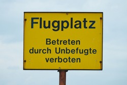 Yellow sign with the inscription: Airfield, forbidden to enter by unauthorized persons, in German language