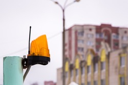Yellow signal lamp with antenna on a metal tube. In the background, out of focus, a lamppost and residential buildings. Gloomy gray sky.