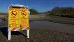 Yellow signs next to dirty puddle warn of dangerous sewage contamination on hiking trail near Tijuana River