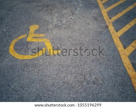 Yellow signs show parking for the disabled on the outdoor asphalt parking lot.physically challenged.