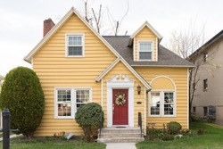 Yellow single family home with red door and floral wreath