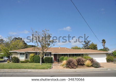 Yellow single family house with grass in front has wires and cables coming off the roof