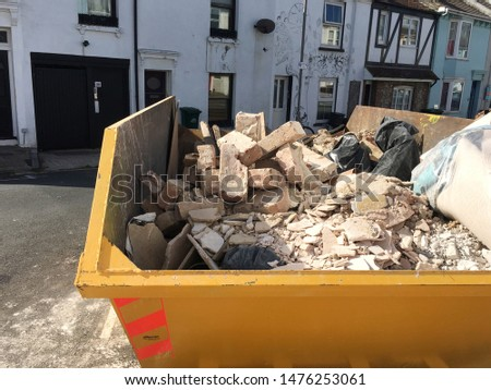 Yellow skip hire filled with rubbles and building waste on street in Brighton