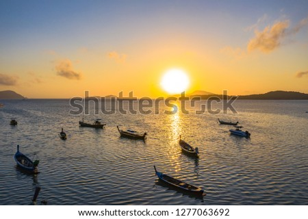 yellow sky during sunrise above fishing boats in Rawai sea Phuket Thailand