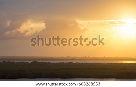 Yellow sky. Sunset over the Caribbean coast. Sun going down and glowing yellow. Image taken from high level. Beautiful wallpaper. #603268553