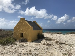 Yellow slave house and blue sky on Caribbean beach - Bonaire Netherlands Antilles
