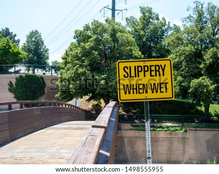 Yellow slippery when wet sign in front of a small wooden foot bridge