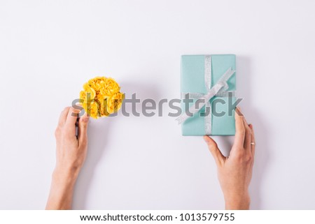 Yellow small roses and blue gift box with a bow in female hands on a white table top view