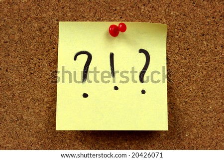 Yellow small sticky note on an office cork bulletin board. Surprise and confusion message.