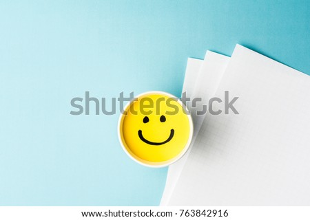 Yellow smiling face, happy mood, on paper cup and papers over blue background.