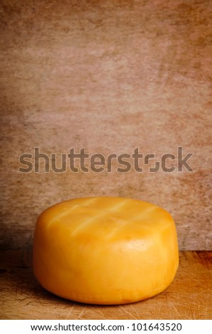 yellow smoked cheese on a vintage grunge wooden background with copy space