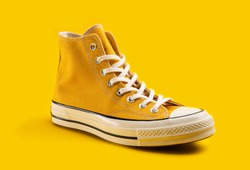 Yellow sneakers on yellow background with copy space. Youth shoes.