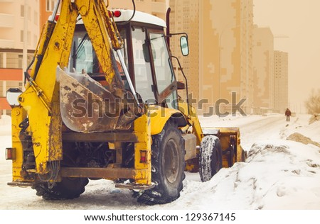 yellow snow plow on an empty street