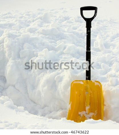 Yellow snow shovel standing in the snow