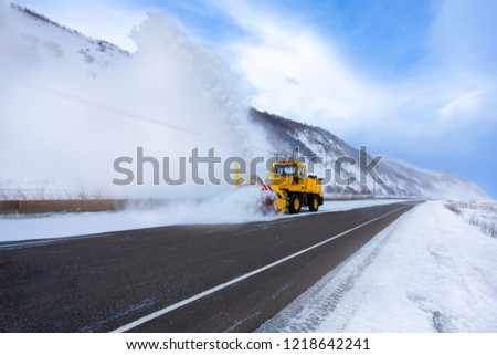 Yellow snowplow truck or snow removal truck with snowplow blade is removing the snow from the highway after cold snowstorm on the winter day.