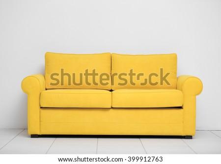 Yellow sofa on white wall background