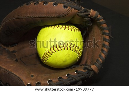 Yellow softball in a catcher's glove
