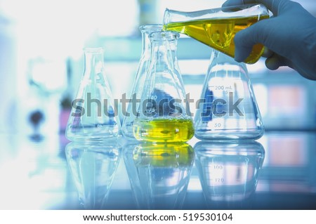 yellow solution in glass flask with scientist hand in research science lab background