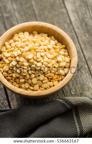 Yellow split peas in bowl on wooden table. #536663167