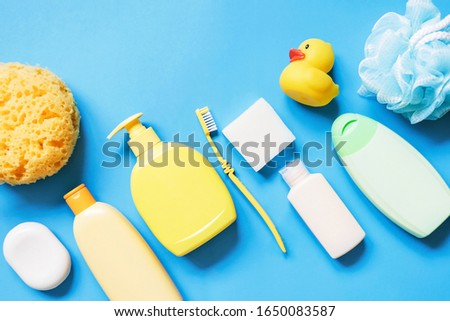 Yellow sponge, soap bar, shampoo bottle, toothbrush, shower gel, hair balm and rubber duck on a blue background. Flat lay photography bath products, baby care cosmetic